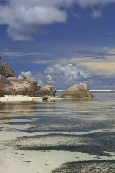 Classic view of the rounded rocks, sandy beach and coral reef of Anse Source d'Argent with storm clouds gathering on the island of La Digue in the Seychelles in Africa
