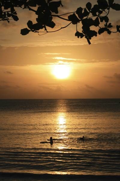 Two boys swim in the Indian Ocean at Beau Vallon Bay as the sun sets in the West of the island of Mahé Mahe in the Seychelles in Africa