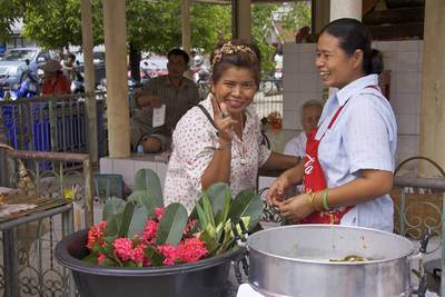 Two lady flower sellers at the market in Klong Mahasawasdi selling Lotus flowers and red flowers in Nakhon Pathom in Thailand
