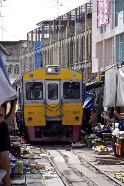 1 of 8 daily trains passes between the market stalls in Risky market in Maeklong, Samut Songkhram in Thailand