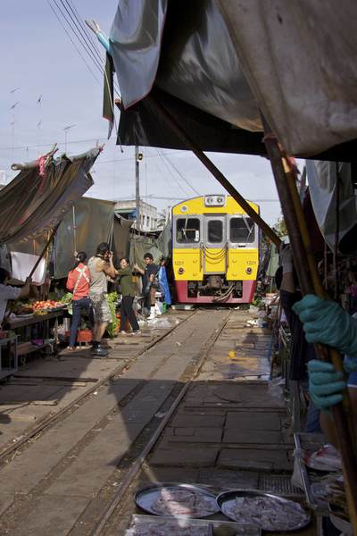 Stall holders re-erect the tarpaulin covers over their stalls next to the railway tracks after the train has passed, in Risky market in Maeklong, Samut Songkhram in Thailand