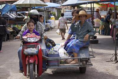 Motorbike and sidecar with 5 passengers driving through Bang Noi village market in Samut Songkhram in Thailand