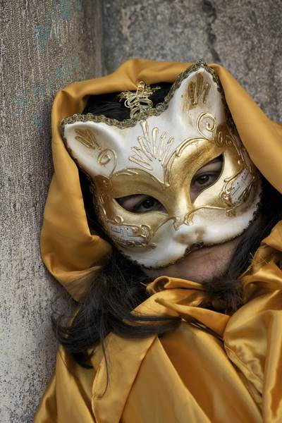 A young carnival goer reveller in a mask and yellow silk cloak rests on the steps in St Marks Square in Venice, Italy, Europe
