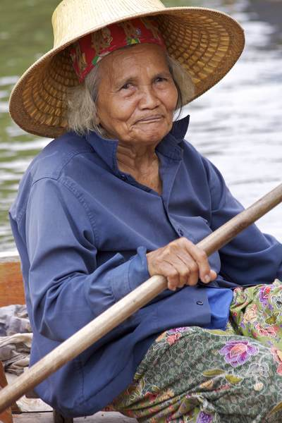 An old lady in traditional hat and dress brings fruit to sell from her boat at the Tha Kha Floating market in Samut Songkhram in Thailand