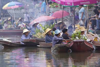 Local woman wearing traditional straw hats arrive at the Tha Kha Floating market to sell a range of vegetables, flowers and freshly cooked food from their boats on the canal, in Samut Songkhram in Thailand