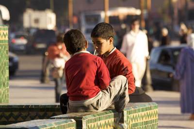 Two young boys talk together in the busy city of Marrakech Marrakesh in Morocco in Africa