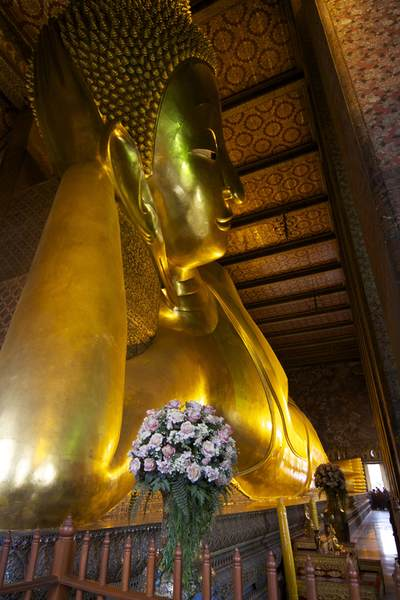 Golden plated head of the reclining Buddha and a view down his body - 46 meters long and 15 meters high, at the Wat Pho temple (Wat Phra Chetuphon) complex in Rattanakosin (Old City) in Bangkok in Thailand