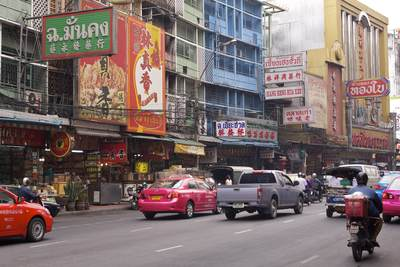 Busy street with colourful taxis and many signs in Chinatown in the Samphanthawong district of Bangkok in Thailand