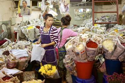 Two women working in a flower stall wrapping roses and Chrysanthemums (mums or chrysanths/Asteraceae) in newspaper with a picture of a member of the Thai Royal family above in the Pak Klong Talat market (flower market) in Bangkok in Thailand