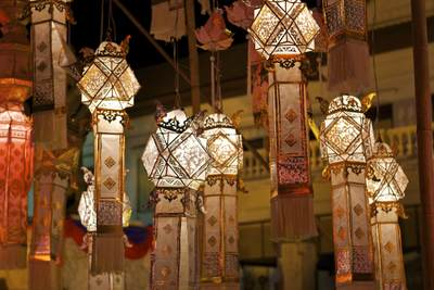 Delicate paper lanna lanterns on display at the November festival of Loy (Loi) Krathon (known locally as Yi Peng) located near the 3-Kings monument in the Old City in Chiang Mai in Thailand