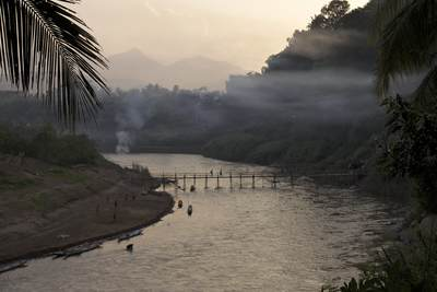 Smoke from small fires collects above a bamboo bridge crossing the Nam Khan river in Luang Prabang at dusk in Laos