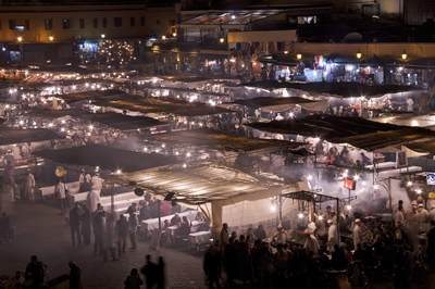 Charcoal smoke rising over the food stalls of Place Jmaa El Fna at night with people eating and market stalls around the edge in Marrakech Marrakesh in Morocco in Africa