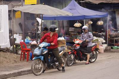 Two local women on mopeds outside the stalls of the early morning food market in Luang Prabang in Laos
