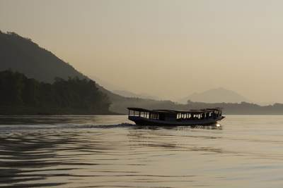 A boat returns to Luang Prabang on the Mekong at sunset with misty jungle in the background in Laos