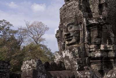 View upwards towards the massive stone faces clustering around the central peak within the Angkor Thom complex (Khmer for Great City) built in the late twelfth century in Cambodia