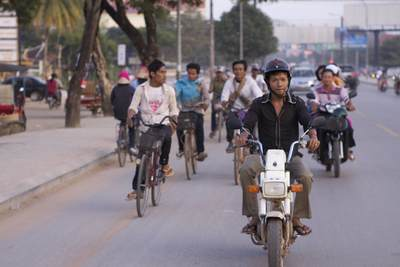 Rush hour with most locals riding mopeds or motorcycles, on National Road no. 6 (Airport Road) in Siem Reap in Cambodia