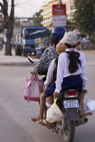 A woman and her two daughters ride home on a moped carrying shopping in bags, along the National Road no. 6 (Airport Road) in Siem Reap in Cambodia