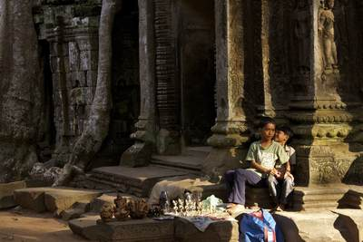 Two Cambodian brothers set up a stall of local crafts and gifts by the outer wall of Ta Prohm - built by the Khmer King Jayavarman VII between  the late 12th and early 13th centuries, originally called Rajavihara near Siem Reap in Cambodia