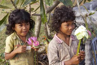 Two sisters selling folded Lotus flowers outside of the Wat Kampong Tralach just outside of the village in Cambodia