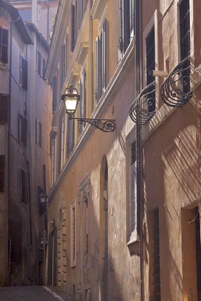 A narrow side street with wrought iron lamp in the early morning haze, located off of Via Dei Coronari in Rome, Lazio in Italy, Europe