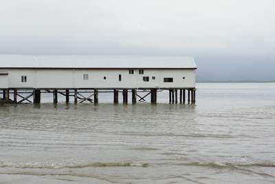 The white painted wooden stilted building of the Port Douglas Sugar Wharf in Port Douglas on a grey tropical day in Queensland, Northern Australia