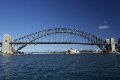 View of the metal Sydney Harbour bridge seen from water on a sunny morning, in New South Wales in Australia