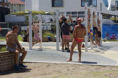 Muscular suntanned men in small budgie smuggler trunks briefs pants work out train in the gym gymnasium next to Bondi Beach in Sydney, New South Wales  in Australia