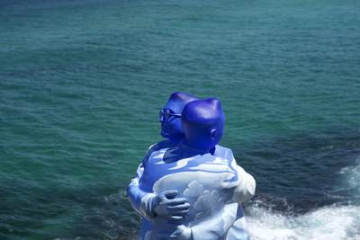 'Under One Sky' by Stephen Marr comprising of two blue figures hugging by the sea, part of the 'Sculpture by the Sea' exhibition at Bondi Beach 2017 in Sydney, New South Wales in Australia