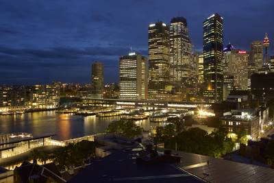 View of the high-rises and sky scrapers with ferries at Circular Quay at dusk in Sydney, New South Wales in Australia