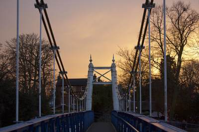 Teddington footbridge and the Anglers pub at sunset on a winters evening in Teddington, Middlesex United Kingdom Europe