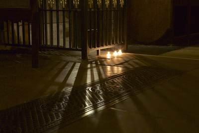 Candles cast shadows of wrought iron railings during a candle light evening at Southwark Cathedral in London United Kingdom