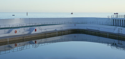 Reflections of the Jubilee Pool lido on Penzance Promenade during very calm weather with the Atlantic sea beyond in Cornwall United Kingdom Europe