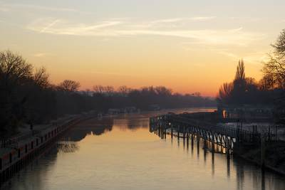 View at dawn upstream of the river Thames from Teddington on a frosty winter morning, with Teddington weir to the right and moored boats, Middlesex, United Kingdom Europe