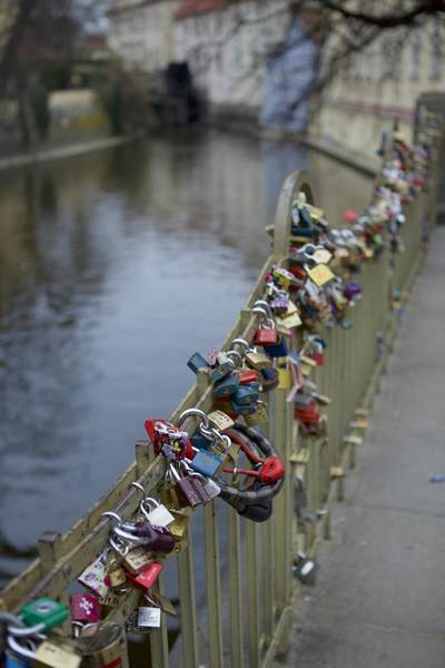 Padlocks of love attached to a wrought iron fence alongside the Vltava river in Prague, Czech Republic in Europe
