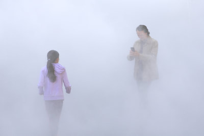 A girl and her father walk through the 'London Fog' art installation by Japanese artist Fujiko Nakaya at the Tate Modern art gallery in London United Kingdom