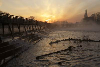 Teddington weir at sunrise dawn in the winter light at very low tide in Teddington, Middlesex in United Kingdom in Europe