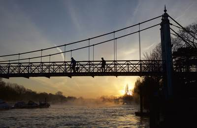 Steam rises on the river Thames at dawn as cyclists and commuters cross Teddington footbridge on a winters morning in Teddington, Middlesex, United Kingdom, Europe