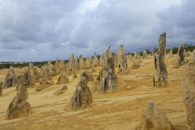 The Pinnacles with the grey clouds of an approaching storm - limestone formations within Nambung National Park, near the town of Cervantes in Western Australia