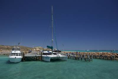 Boats moored on the Exmouth peninsula in North West Australia on the blue Indian Ocean, next to the Ningaloo reef