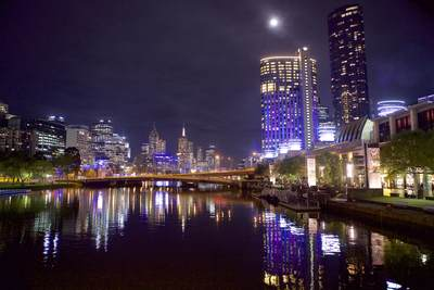 View of Melbourne city high-rises and sky scrapers at night from the Spencer Bridge looking towards the East and West banks and Yarra Promenade over the Yarra River with the Crown Casino to the right in Victoria,  Australia