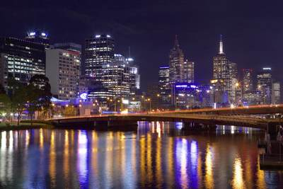 View of Melbourne city high-rises and sky scrapers at night from the Spencer Bridge looking towards the West bank and Yarra Promenade over the Yarra River in Victoria,  Australia