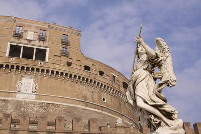 Red brick exterior of Castel Sant'Angelo, built in 135 by Hadrian as his mausoleum, with one of 10 angel sculptures on the Ponte Sant'Angelo (Aelian Bridge or Pons Aelius) - the sculpture entitled 'Angel with the Lance' by Domenico Guidi in Rome, Lazio, Italy Europe