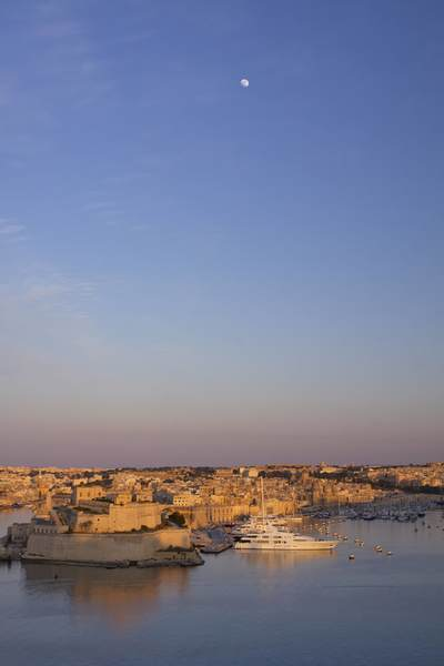 View of Dockyard Creek and Birgu (Vittoriosa) in the Grand Harbour with the moon above at sunset in Valletta in Malta Europe