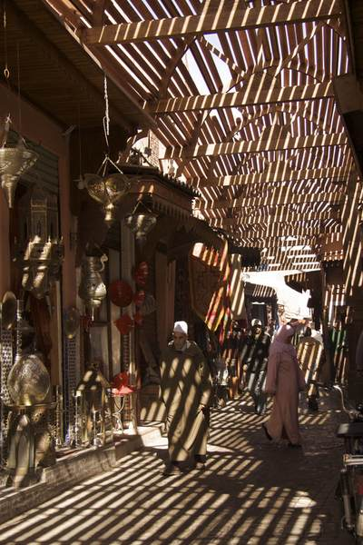 Light falls in shafts through the trellised roof of the 'Dyers' souk - Souk Sabbaghine - in the Northern Medina on a man and woman shopping in Marrakech Marrakesh in Morocco in Africa