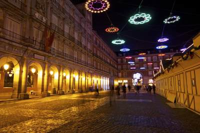 Christmas lights strung above the cobbled Plaza Mayor facing towards the arch leading to Calle Postas in Madrid in Spain, Europe