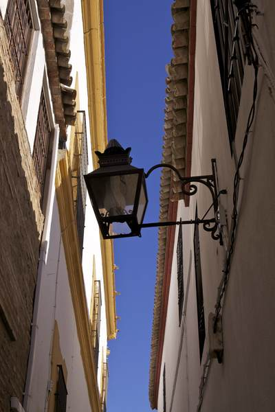 View skywards in a narrow lane with wrought iron lamp and colourful paintwork in Cordoba in Andalusia in Spain, Europe