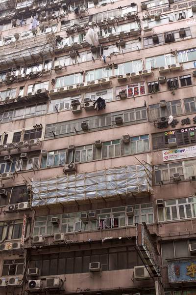 Dirty and pollution stained tenement buildings with air. con. units and laundry on the exterior, in the Mong Kok district of the Kowloon Peninsula in Hong Kong