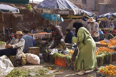 Women wearing jellabas and scarves shopping for fruit and vegetables from male stall holders in a local market in the Northern medina of Marrakech Marrakesh in Morocco in Africa