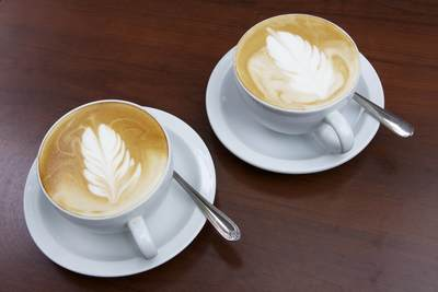 Two cups of Flat White coffee - the signature coffee of New Zealand with the silver fern motif in latte art on top