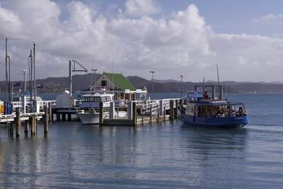 The pier at Russell with Paihia in the background and the passenger ferry 'Waitere' approaching on North Island New Zealand